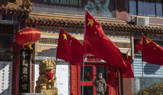 """In this photo taken Tuesday, March 3, 2020, a worker stands near Chinese national flag and propaganda which reads """"Go China"""" in Beijing. As the rest of the world grapples with a burgeoning virus outbreak, China's ruling Communist Party has turned to its propaganda playbook to portray its leader as firmly in charge, leading an army of health workers in a """"people's war"""" against the disease. (AP Photo/Ng Han Guan)"""