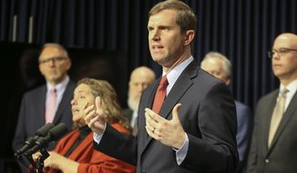 Governor Andy Beshear speaks at the podium at a press conference on the Corona virus and Kentucky's steps to combat the outbreak, Mar. 9, 2020, at the capitol in Frankfort, Kentucky. (Michael Clevenger/Courier Journal via AP)
