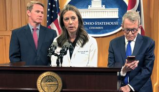 """Dr. Amy Acton, Ohio Department of Health Director, center, discusses the confirmation of Ohio's first three cases of coronavirus, as Gov. Mike DeWine, right, studies an update on the cases provided to him during a news conference, Monday, March 9, 2020, in Columbus, Ohio. Lt. Gov. Jon Husted is at left. Acton said the state is """"leaning in and taking an aggressive approach"""" to combating the disease. (AP Photo/Andrew Welsh-Huggins)"""