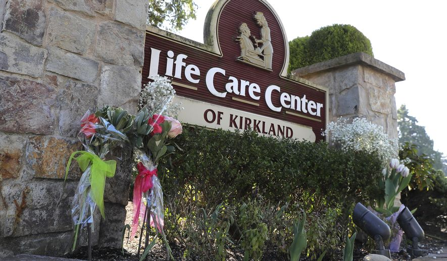 Flowers left next to the sign that marks the entrance to the parking lot of the Life Care Center in Kirkland, Wash. are shown Monday, March 9, 2020, near Seattle. The nursing home is at the center of the outbreak of the COVID-19 coronavirus in Washington state. (AP Photo/Ted S. Warren)