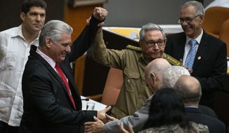 Raul Castro, First Secretary of the Communist Party and former president raises the hand of Cuba's president Miguel Diaz-Canel, right, during the closing session at the National Assembly of Popular Power in Havana, Cuba, Saturday, Dec. 21, 2019. (AP Photo / Ramon Espinosa)
