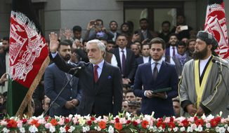 In this Monday, March 9, 2020, photo, Afghanistan's Abdullah Abdullah, front left, greets his supporters after being sworn in as president in Kabul, Afghanistan. Washington moved forward Tuesday on its peace deal with the Taliban, launching its troop withdrawal, while praising Afghanistan's newly installed President Ashraf Ghani's promise to proceed with a Taliban prisoner release as well as cobble together a team to start negotiations with the insurgent group. But the dueling presidential inaugurations a day earlier with Ghani's rival, Abdullah Abdullah also being sworn in as president is indicative of the uphill task facing Washington's peace envoy Zalmay Khalilzad as he tries to get Afghanistan's bickering leadership to come together.  (AP Photo)