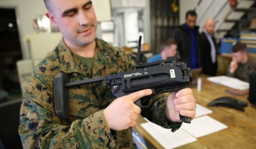 Capt. Nick Berger, project officer in Infantry Weapons at Marine Corps Systems Command, examines the M320A1 grenade launcher in March 2019. (Image: U.S. Marine Corps, Joseph Neigh, released)