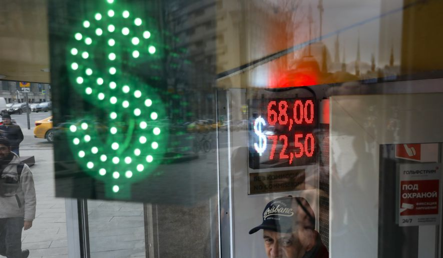 A man stands at an exchange office screen showing the currency exchange rates of U.S. Dollar and Euro to Russian Rubles in Moscow, Russia, Tuesday, March 10, 2020. Oil prices are plunging after Saudi Arabia started a price war against Russia. The Saudis tried to get the Russians to cut oil production to keep prices from falling even more due to the coronavirus. (AP Photo/Pavel Golovkin)