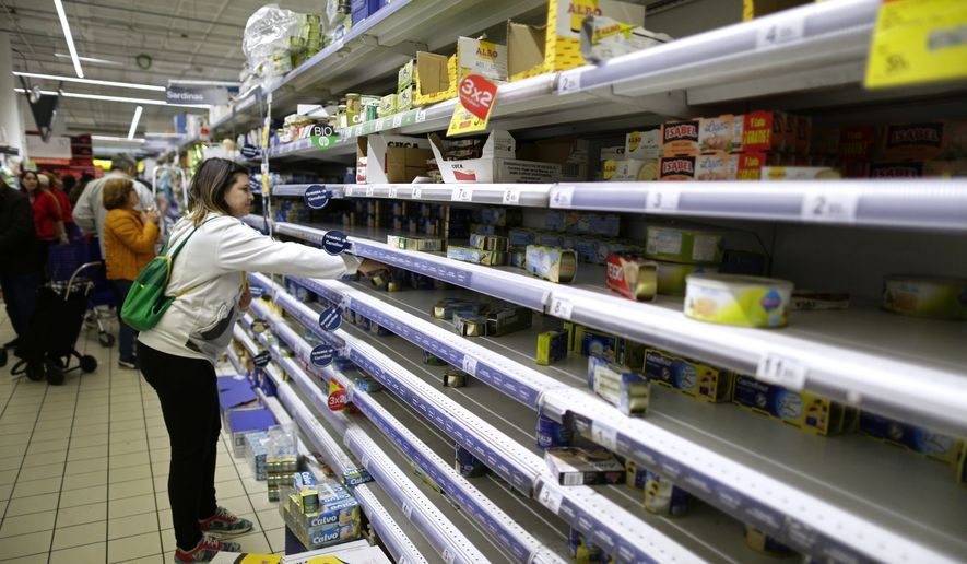 Empty shelves are seen in a supermarket as people begin to stock up on provisions in Madrid, Spain, Tuesday, March 10, 2020.  People have emptied shelves of food and supplies in supermarkets in Madrid after Spain's health minister on Monday announced a sharp spike in coronavirus cases in and around the national capital, and said all schools in the region, including kindergartens and universities, will close for two weeks from Wednesday.  (AP Photo/Manu Fernandez)