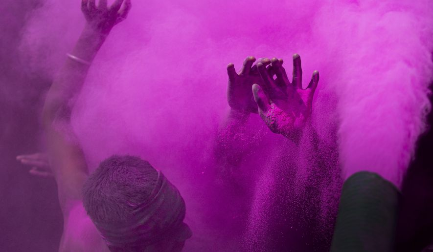 Indians dance and throw colored powder during Holi festival celebrations in Gauhati, India, Tuesday, March 10, 2020. The festival heralds the arrival of spring. (AP Photo/Anupam Nath)