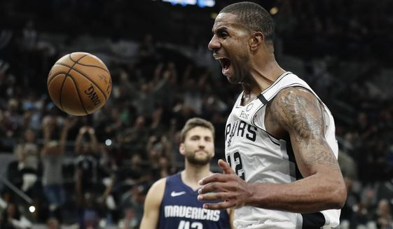 San Antonio Spurs forward LaMarcus Aldridge (12) celebrates as he scores against the Dallas Mavericks during the second half of an NBA basketball game in San Antonio, Tuesday, March 10, 2020. (AP Photo/Eric Gay)