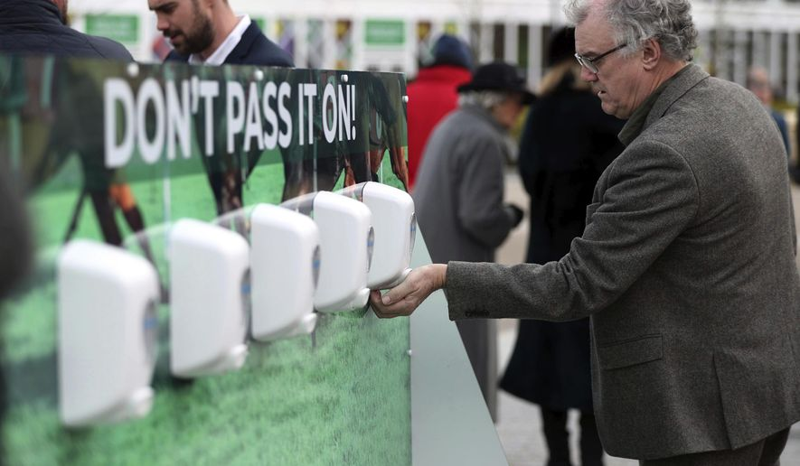Racegoers use hand sanitizer to help prevent the spread of coronavirus, on day one of the Cheltenham Festival at Cheltenham Racecourse, Cheltenham, England, Tuesday, March 10, 2020. (Simon Cooper/PA via AP)