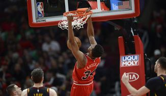Chicago Bulls' Wendell Carter Jr. (34) dunks next to Cleveland Cavaliers' Kevin Love (0) during the first half of an NBA basketball game Tuesday, March 10, 2020, in Chicago. (AP Photo/Paul Beaty)