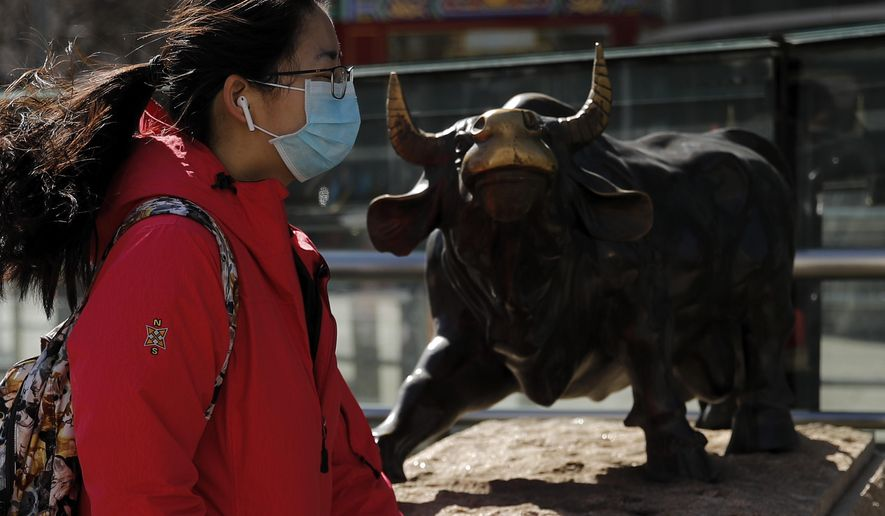 A woman wearing a protective face mask walks by the investment icon bull statue on display outside a bank in Beijing, Tuesday, March 10, 2020. Asian stock markets took a breather from recent steep declines on Tuesday, with several regional benchmarks gaining more than 1% after New York futures reversed on news that President Donald Trump plans to ask Congress for a tax cut and other quick measures to ease the pain of the virus outbreak. (AP Photo/Andy Wong)