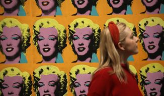 """CAPTION CORRECTS NAME OF ARTWORK A Tate representative poses for photographs next to the 1962 Andy Warhol piece""""Marilyn Diptych"""", during a media preview for the exhibition """"Andy Warhol"""" at the Tate Modern gallery in London, Tuesday, March 10, 2020. The exhibition, which runs from March 12 to September 6, features over 100 works spanning the American artist's career in the second half of the 20th century until his death in 1987. (AP Photo/Matt Dunham)"""
