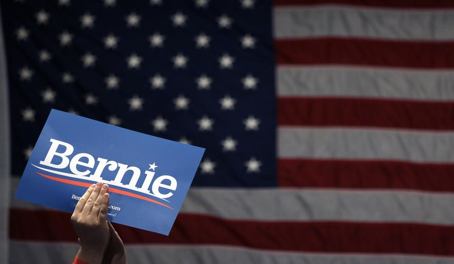 A supporter of Democratic presidential candidate Sen. Bernie Sanders, I-Vt., applauds as Sanders speaks during a campaign rally Monday, March 9, 2020, in St. Louis. (AP Photo/Jeff Roberson)
