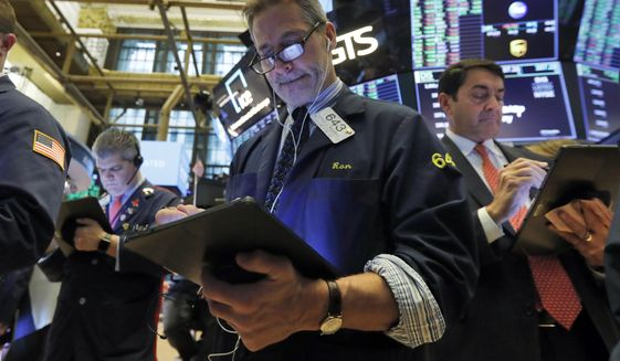 Trader Ronald Madarasz, center, works on the floor of the New York Stock Exchange, Tuesday, March 10, 2020. Stocks, Treasury yields and oil are clawing back some of the plunge they took a day before, when the S&P 500 had its worst drop in more than a decade. (AP Photo/Richard Drew)