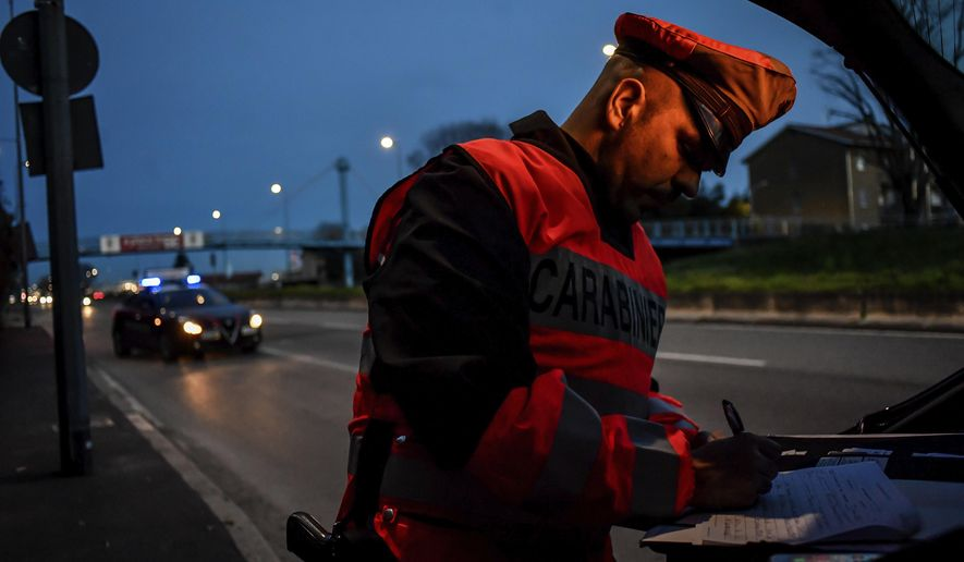 A policeman checks cars entering Milan, Northern Italy, Tuesday, March 10, 2020. People moving from one place to another must certificate they are doing it for work or important personal or health reasons, following the latest measures to slow down the diffusion of the new Coronavirus. For most people, the new coronavirus causes only mild or moderate symptoms, such as fever and cough. For some, especially older adults and people with existing health problems, it can cause more severe illness, including pneumonia. (Claudio Furlan/LaPresse via AP)