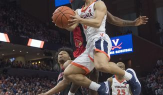 Virginia guard Kihei Clark drives to basket as Louisville's Darius Perry defends during the second half of an NCAA college basketball game in Charlottesville, Va., Saturday, March 7, 2020. (AP Photo/Lee Luther Jr.)