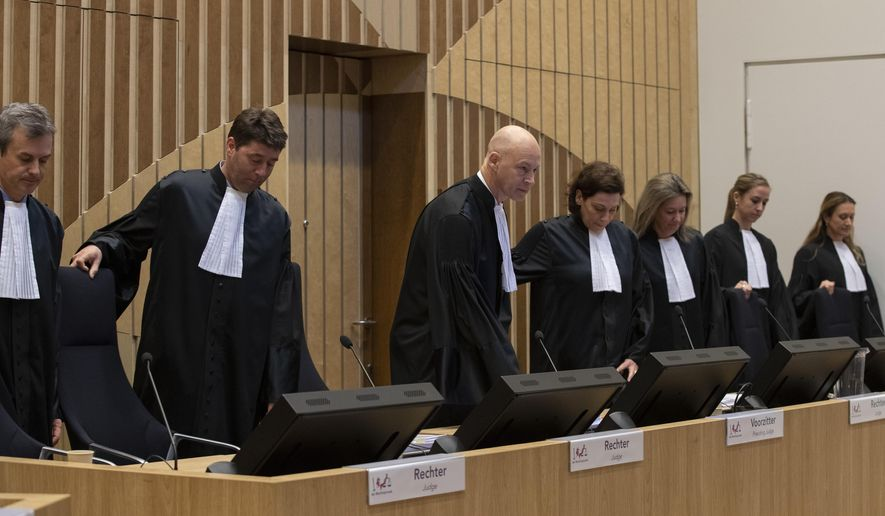 Presiding judge Hendrik Steenhuis, third from left, and other judges take their seats in court on the second day of the trial of four men charged with murder over the downing of Malaysia Airlines flight 17, at Schiphol airport, near Amsterdam, Netherlands, Tuesday, March 10, 2020. A missile fired from territory controlled by pro-Russian rebels in Ukraine in 2014, tore the MH17 passenger jet apart killing all 298 people on board. (AP Photo/Peter Dejong)
