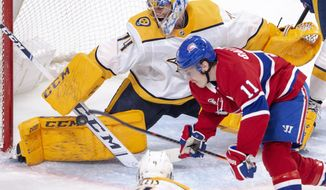 Nashville Predators goaltender Juuse Saros (74) makes a save on Montreal Canadiens right wing Brendan Gallagher (11) during the third period of an NHL hockey game Tuesday, March 10, 2020, in Montreal. (Ryan Remiorz/The Canadian Press via AP)