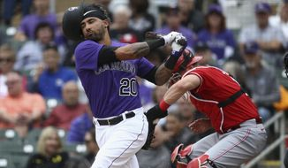 Colorado Rockies' Ian Desmond (20) loses his helmet on a swing as Cincinnati Reds catcher Curt Casali, right, gets out of the way during the second inning of a spring training baseball game Tuesday, March 10, 2020, in Scottsdale, Ariz. (AP Photo/Ross D. Franklin)