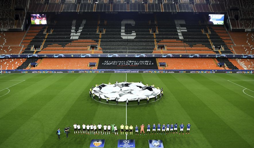 Atalanta and Valencia players line up ahead of the Champions League round of 16 second leg soccer match between Valencia and Atalanta in Valencia, Spain, Tuesday March 10, 2020. The match is being in an empty stadium because of the coronavirus outbreak. (UEFA via AP)