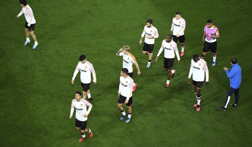 Valencia players warm up ahead of the Champions League round of 16 second leg soccer match between Valencia and Atalanta in Valencia, Spain, Tuesday March 10, 2020. The match is being in an empty stadium because of the coronavirus outbreak. (UEFA via AP)