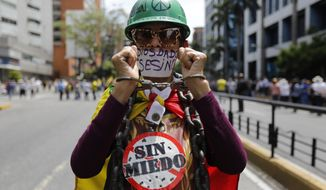 """A member of the opposition holds up her handcuffed hands as she joins the start of a rally in Caracas, Venezuela, Tuesday, March 10, 2020. Her signs read in Spanish """"No fear,"""" and """"Diosdado assassin,"""" referring to ruling party politician Diosdado Cabello. U.S.-backed Venezuelan political leader Juan Guaido will lead a march aimed at retaking the National Assembly legislative building, which opposition lawmakers have been blocked from entering. (AP Photo/Ariana Cubillos)"""