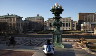 A woman sits on the Columbia University campus, Monday, March 9, 2020, in New York. Colleges nationwide, including Columbia, are shutting down campuses with plans to continue instruction online, leaving some students distressed over where to go and professors puzzling over how to keep up higher education as they know it in the time of coronavirus. Dozens of colleges have canceled in-person classes temporarily or the balance of the semester.  (AP Photo/Mark Lennihan)