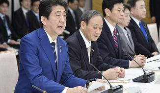 Japan's Prime Minister Shinzo Abe, left, speaks during a meeting on countermeasures against the new coronavirus infections at his official residence in Tokyo Tuesday, March 10, 2020. For most people, the new coronavirus causes only mild or moderate symptoms, such as fever and cough. For some, especially older adults and people with existing health problems, it can cause more severe illness, including pneumonia. The vast majority of people recover from the new virus. (Yoshitaka Sugawara/Kyodo News via AP)