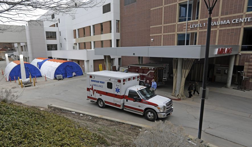 Negative pressure tents, left, are shown outside the University of Utah's hospital, Monday, March 9, 2020, in Salt Lake City. The hospital is taking steps to limit the spread of the new coronavirus, including new visitor policies and the construction of outdoor negative pressure tents where people can be tested without having to go inside the hospital building. (AP Photo/Rick Bowmer)