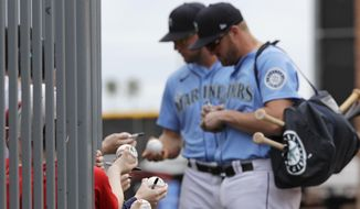 Seattle Mariners' Connor Lien, left, and Mitch Nay stop to sign autographs before a spring training baseball game against the Los Angeles Angels on Tuesday, March 10, 2020, in Peoria, Ariz. (AP Photo/Elaine Thompson) **FILE**