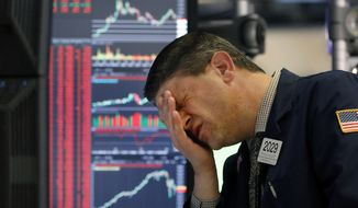 Trader Michael Gallucci works at his post on the floor of the New York Stock Exchange, Wednesday, March 11, 2020. Stocks are closing sharply lower on Wall Street, erasing more than 1,400 points from the Dow industrials, as investors wait for a more aggressive response from the U.S. government to economic fallout from the coronavirus. (AP Photo/Richard Drew)