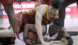 Iowa State forward Michael Jacobson, top, and Oklahoma State forward Cameron McGriff, bottom, hit the floor after the ball during the first half of an NCAA college basketball game in the first round of the Big 12 men's basketball tournament in Kansas City, Kan., Wednesday, March 11, 2020. (AP Photo/Orlin Wagner)