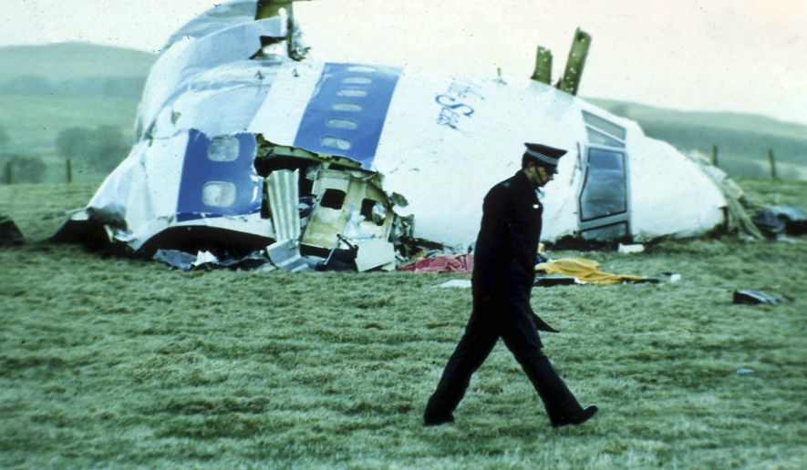 In this December 1988 file photo, a police officer walks past the wreckage in Lockerbie, Scotland, of Pan Am Flight 103 from London to New York. Scotland's criminal appeals body said Wednesday, March 11, 2020, that the family of the Libyan man jailed for the 1988 bombing of an airliner over the Scottish town of Lockerbie can launch a posthumous appeal against his conviction. (AP Photo/File)