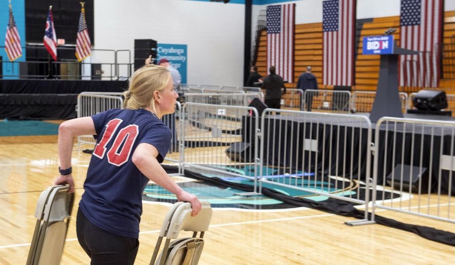 A worker carries chairs after a campaign rally for Democratic presidential candidate former Vice President Joe Biden was cancelled at Cuyahoga Community College Tuesday, March 10, 2020, in Cleveland, due to health concerns with the coronavirus. (AP Photo/Phil Long)