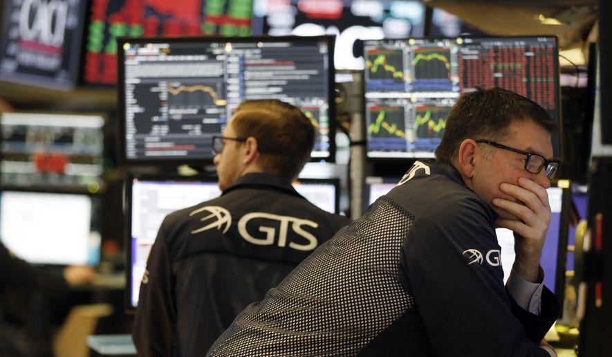 Specialist David Haubner, right, works on the floor of the New York Stock Exchange, Wednesday, March 11, 2020. Stocks are closing sharply lower on Wall Street, erasing more than 1,400 points from the Dow industrials, as investors wait for a more aggressive response from the U.S. government to economic fallout from the coronavirus. (AP Photo/Richard Drew)