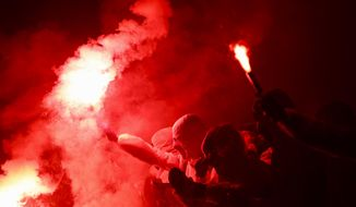 PSG supporters holding up flares gather as the bus with PSG soccer players arrive prior a Champions League round of 16 second leg soccer match between Paris-Saint-Germain and Borussia Dortmund at the Parc des Princes stadium in Paris Wednesday, March 11, 2020. The match is played behind closed doors without spectators due to the COVID-19 outbreak. For most people, the new coronavirus causes only mild or moderate symptoms, such as fever and cough. For some, especially older adults and people with existing health problems, it can cause more severe illness, including pneumonia. (AP Photo/Christophe Ena)