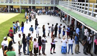 People line up to vote during presidential elections in Georgetown, Guyana, Monday, March. 2, 2020. Guyana get to choose for a new government in a bruising fight for control of a South American country whose oil revenues in the next decade could make it one of the wealthiest in the hemisphere. (AP Photo/Adrian Narine)