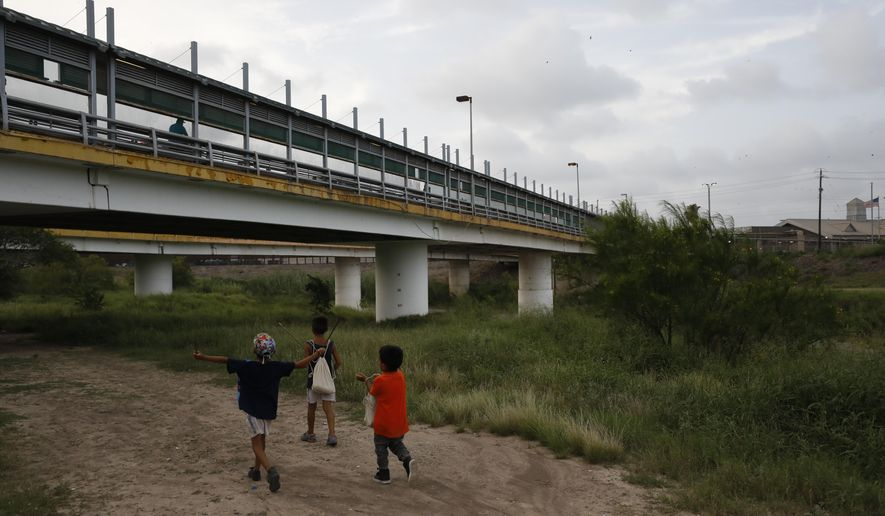 In this June 26, 2019, file photo, migrant children walk with their families along the Rio Grande, as pedestrian commuters use the Puerta Mexico bridge to enter Brownsville, Texas, seen from Matamoros, Tamaulipas state, Mexico.  (AP Photo/Rebecca Blackwell, File)  ** FILE **