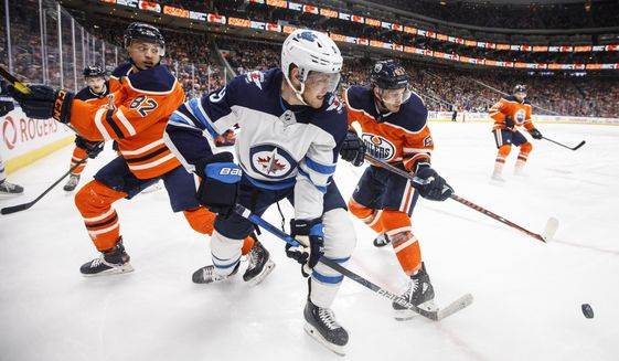 Winnipeg Jets' Andrew Copp (9) works for the puck against Edmonton Oilers' Caleb Jones (82) and Tyler Ennis (63) during the third period of an NHL hockey game Wednesday, March 11, 2020, in Edmonton, Alberta. (Jason Franson/The Canadian Press via AP)