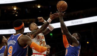 Atlanta Hawks forward John Collins (20) battles New York Knicks forward Julius Randle (30) as he drives to the basket during the first half of an NBA basketball game Wednesday, March 11, 2020, in Atlanta. (AP Photo/John Bazemore)