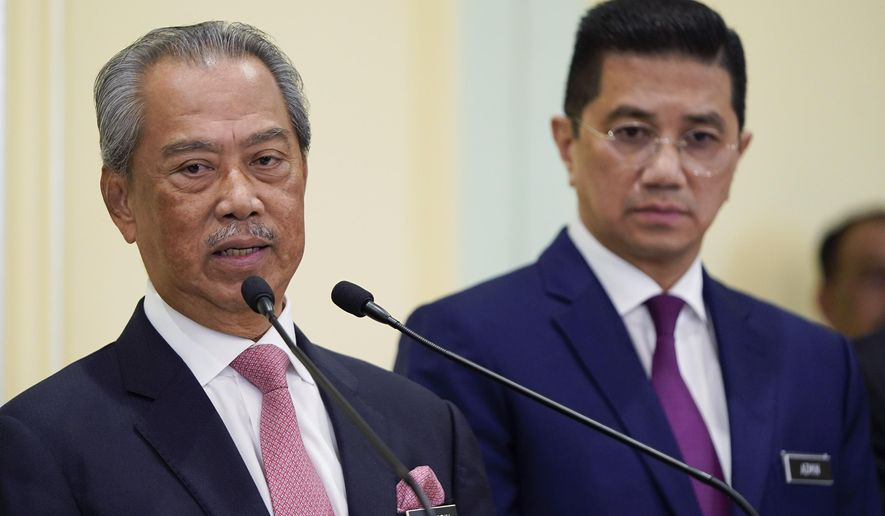 Malaysian new Prime Minister Muhyiddin Yassin, left, speaks next to Senior Minister Azmin Ali during a press conference after the first cabinet meeting at prime minister's office in Putrajaya, Malaysia Wednesday, March 11, 2020. Yassin said he will form an economic council to find ways to cope with an expected economic slowdown amid the global new coronavirus outbreak. (AP Photo/Vincent Thian)