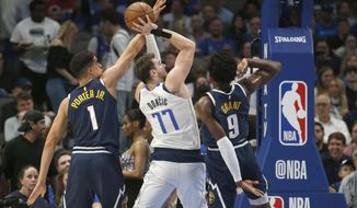 Dallas Mavericks guard Luka Doncic (77) shoots as Denver Nuggets forwards Michael Porter Jr. (1) and Jerami Grant (9) defend during the first half of an NBA basketball game Wednesday, March 11, 2020, in Dallas. (AP Photo/Ron Jenkins)
