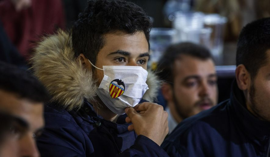 Valencia supporters watch the match in a TV sitting in a terrace outside Mestalla stadium during the Champions League round of 16 second leg soccer match between Valencia and Atalanta in Valencia, Spain, Tuesday March 10, 2020. The match is being in an empty stadium because of the coronavirus outbreak. (AP Photo/Emilio Morenatti)
