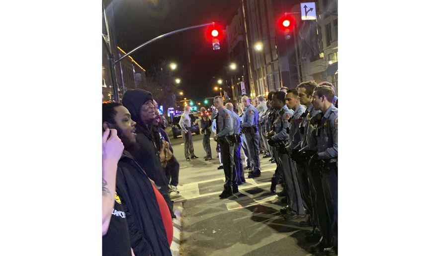Demonstrators come face to face with police at an intersection in Raleigh, North Carolina, during a protest Wednesday, March 11, 2020, Raleigh Police said in a statement that an officer shot a man after a foot chase on Tuesday. (Courtesy of Kerwin Pittman via AP)
