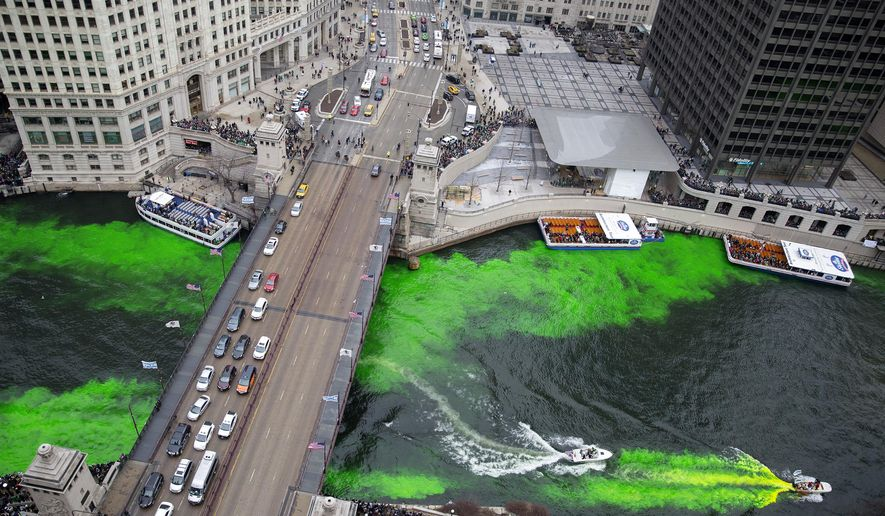 FILE - In this March 17, 2018 file photo, boats move through the water as the Chicago River is dyed green for St. Patrick's Day in Chicago. Chicago on Wednesday, March 11, 2020 joined the growing ranks of cities across the United States to cancel its Saturday St. Patrick's Day Parade amid concerns about the coronavirus. The city will not be dyeing the river green either. For most people, the new coronavirus causes only mild or moderate symptoms, such as fever and cough. For some, especially older adults and people with existing health problems, it can cause more severe illness, including pneumonia. (Erin Hooley/Chicago Tribune via AP File)