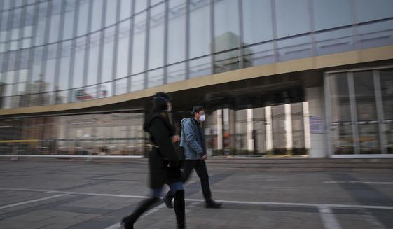 People wearing protective face masks walk by a quiet Silk Street Mall, a usually popular tourist spot before the new coronavirus outbreak in Beijing, Wednesday, March 11, 2020. For most, the coronavirus causes only mild or moderate symptoms, such as fever and cough. But for a few, especially older adults and people with existing health problems, it can cause more severe illnesses, including pneumonia. (AP Photo/Andy Wong)