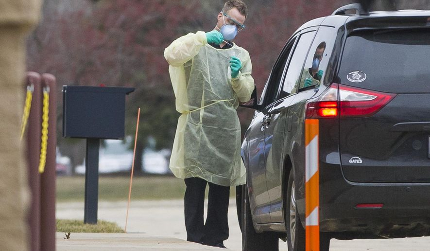 A health care worker tests a patient for the coronavirus in a drive-through site setup outside the South Bend Clinic Day Road Immediate Care Center on Wednesday, March 11, 2020, in Mishawaka, Ind. (Robert Franklin/South Bend Tribune via AP)