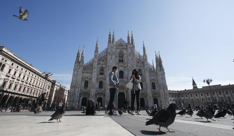 FILE - In this March 8, 2020, file photo, people wear mask as they stand in Duomo Square, in downtown Milan, Italy. Italian Premier Giuseppe Conte's decision to lock down his entire country brought some welcome clarity to life in Italy after weeks of uncertainty about how to behave in a time of coronavirus, according to Associated Press reporter Colleen Barry. (AP Photo/Antonio Calanni, File)