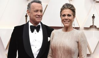 """FILE - In this Feb. 9, 2020 file photo, Tom Hanks, left, and Rita Wilson arrive at the Oscars at the Dolby Theatre in Los Angeles. The couple have tested positive for the coronavirus, the actor said in a statement Wednesday, March 11. The 63-year-old actor said they will be """"tested, observed and isolated for as long as public health and safety requires."""" (Photo by Jordan Strauss/Invision/AP, File)"""