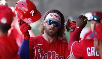 Philadelphia Phillies' Bryce Harper is met in the dugout after being pulled for a pinch runner during a spring training baseball game against the New York Yankees Monday, March 9, 2020, in Clearwater, Fla. (AP Photo/Carlos Osorio)