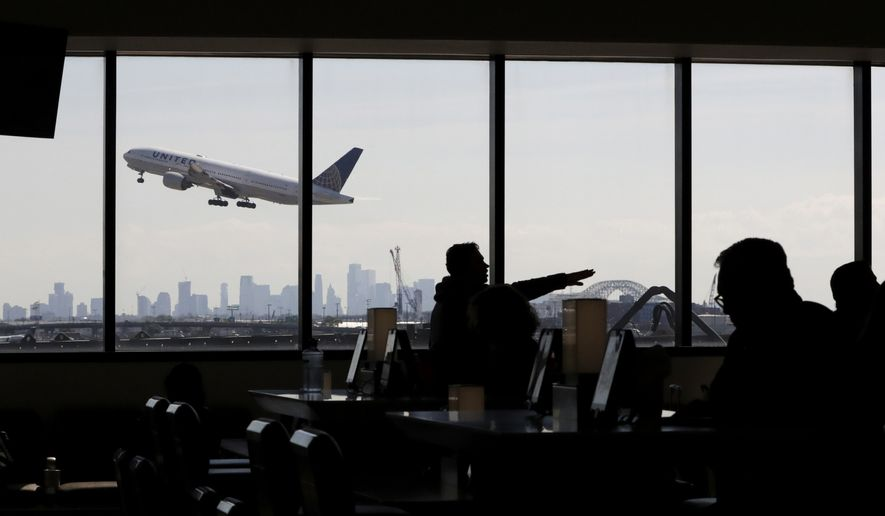 In this July 18, 2018, file photo, a United Airlines commercial jet takes off as travelers sit at a gate in Terminal C of Newark Liberty International Airport in Newark, N.J.  Airlines are stuck in a severe patch of turbulence as the virus outbreak causes passengers to cut back on travel, clouding the industry's growth prospects. All big U.S. airlines have warned investors that their finances will take a hit, and many are cancelling flights because of slumping demand.(AP Photo/Julio Cortez, File)